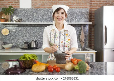 chef with mortar, An Asian woman chef smiling cooking with Thai mortar in the kitchen