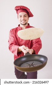 Chef with pan flips pancake in studio shot with red uniform