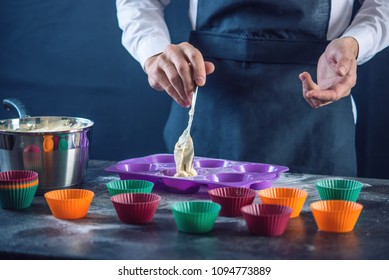 Chef pastry in a black apron filling the dough into a cupcake silicone mold on dark background. Concept of confectionery cooking