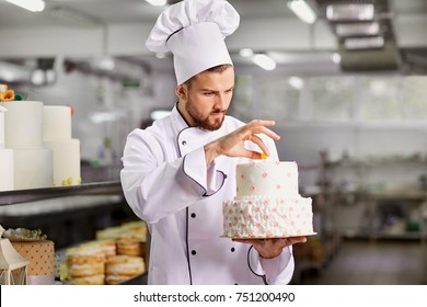 Chef pastry decorates cake in the kitchen.
