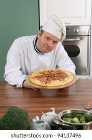 Chef the pizza master holding his product and showing it gentle to you