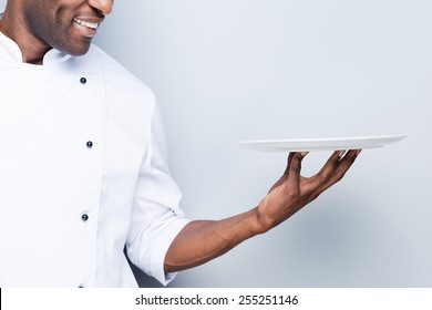 Chef with plate. Close-up of confident young African chef in white uniform holding empty plate and smiling while standing against grey background