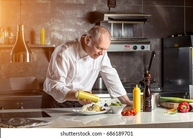 Chef plating up food in a restaurant pouring a gravy or sauce over the meat before serving it to the customer, close up view of his hand and the gravy boat