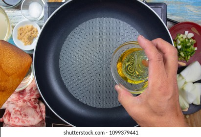 Chef poring oil to pan for cooking / Japanese food cooking Gyudon concept
