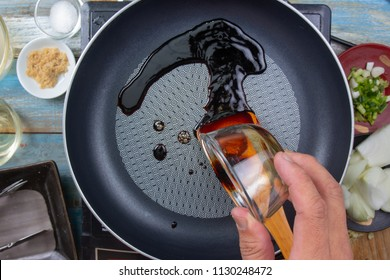Chef poring soy sauce to pan for cooking / Japanese food cooking Gyudon concept