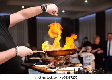 Koch, der Alkohol in eine Bratpfanne mit Feuer gießt