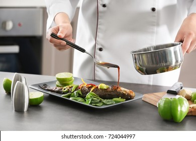 Chef pouring fish with delicious sauce in restaurant