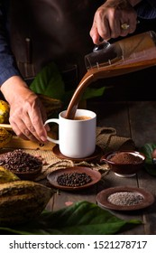 Chef pouring hot Chocolate drink in white cup with ingredient  on wooden dark background .pepper / Cocoa powder / Cocoa bean / fresh Cocoa . Concept chef with hot Chocolate