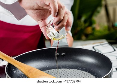 chef pouring oil in to the frying pan for cooking