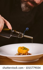 Chef pouring olive oil into the food in a kitchen. Image with bl