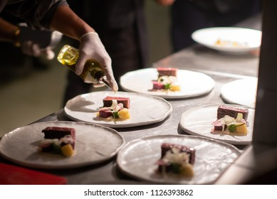 Chef pouring olive oil on creative beef steak
