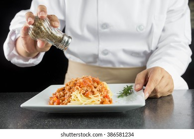 chef pouring Oregano in spaghetti
