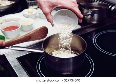 Chef is pouring rice in stewpan, toned image