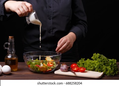 Chef pouring sauce on caesar salad, cooking process, restaurant concept