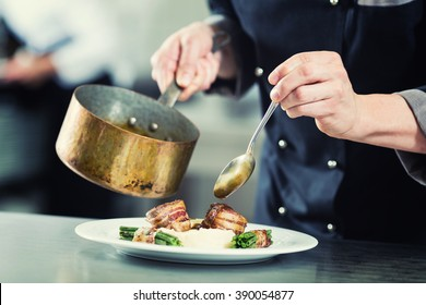 Chef pouring sauce on dish in restaurant kitchen, crop on hands, filtered image