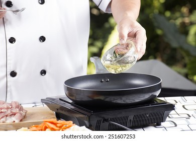 Chef pouring vegetable oil to the pan / cooking Japanese pork curry concept