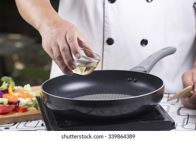 Chef pouring vegetable oil to the pan / Stir fried vegetable concept
