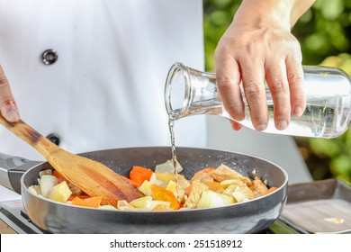 chef pouring  water in to the frying pan for cooking
