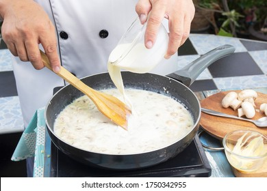 Chef pouring whipping cream in the pan for cooking mushroom cream soup / Cooking Mushroom Cream Soup concept