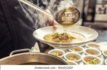 Chef pours broth into a chicken soup with noodles, meat and vegetable.