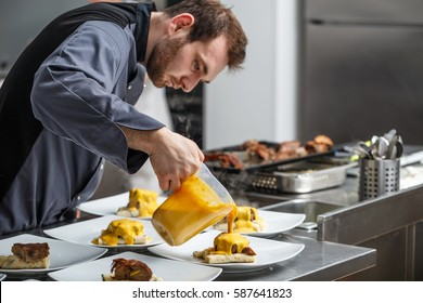 Chef pours a gamy sauce on plate
