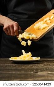 The chef pours pineapple in a plate. For the preparation of pizza, salad. A concept of delicious food and healthy food. On a black background for design or lettering text.