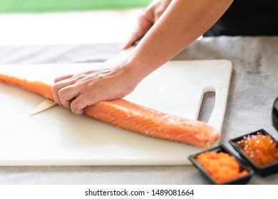 Chef prepare to cut raw salmon. Asian woman chef in black uniform, trying to complete the skinning process of salmon.