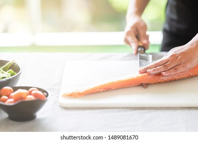 Chef prepare to cut raw salmon. Asian woman chef in black uniform, slicing halfway of raw salmon with light leaks.
