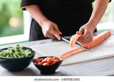 Chef prepare to cut raw salmon. Asian woman chef in black uniform, cutting skin of salmon.