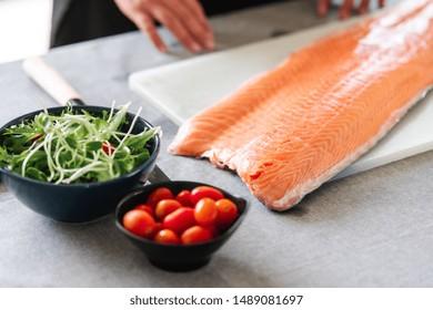 Chef prepare to cut raw salmon. Asian woman chef in black uniform, putting raw salmon on cutting board.