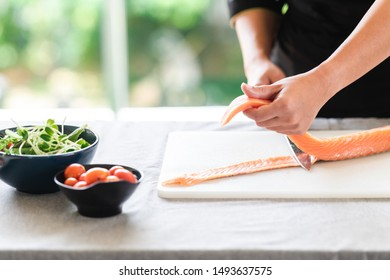 Chef prepare to cut raw salmon. Asian woman chef in black uniform, lifting up the salmon meat.