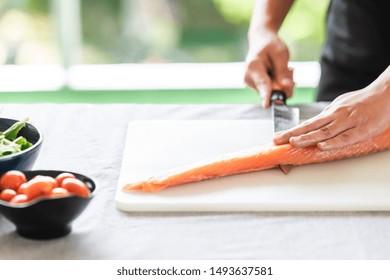 Chef prepare to cut raw salmon. Asian woman chef in black uniform, slicing halfway of raw salmon..
