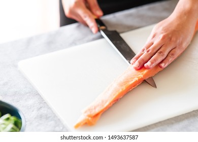 Chef prepare to cut raw salmon. Asian woman chef in black uniform, slicing portion of raw salmon for sushi.