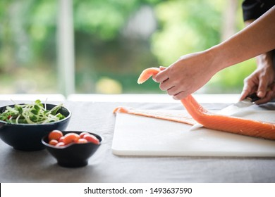Chef prepare to cut raw salmon. Asian woman chef in black uniform, cutting skin of salmon with green background.