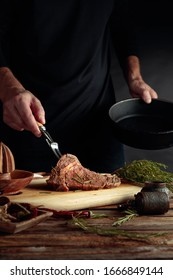 Chef prepare steak. Uncooked steak in sauce with spices an rosemary on a old wooden table.