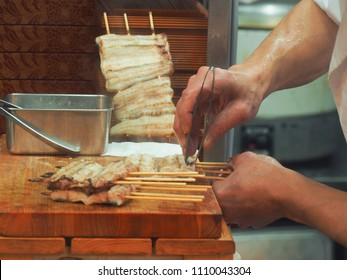 Chef prepare Unadon,Unagi donburi ,eel,Consists of donburi type bowl filled with rice topped with fillets eel (unagi) grilled in a style known as kabayaki.Chef removes fish bone from grilled eel