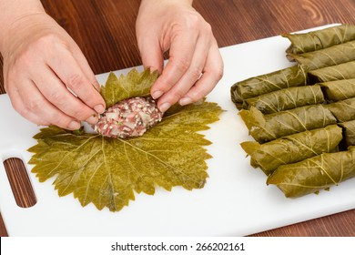 chef prepares cabbage rolls with grape leaves closeup