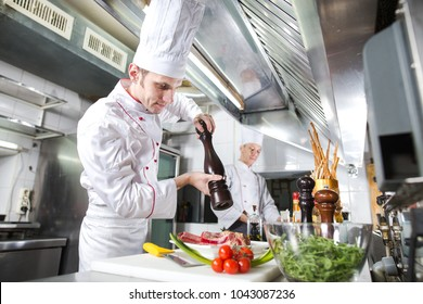 The chef prepares a dish in the kitchen of restoran.
