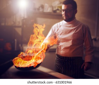 The chef prepares the dish on the stove with an open fire in the kitchen of the restaurant. The photo is blurry, soft focus and lens flare.