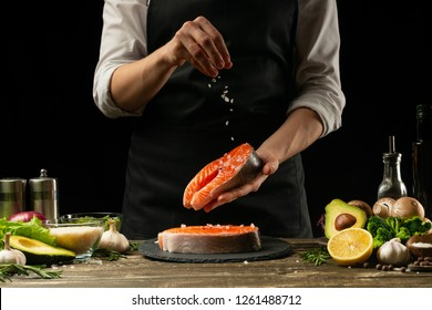 The chef prepares fresh fish salmon, trout, sprinkles with sea salt and vegetables. Horizontal photo. Concept cooking healthy and vegan cuisine, clean food, restaurants, hotel business