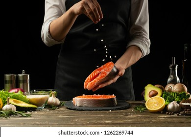 The chef prepares fresh salmon fish, smorgu trout, sprinkling salt with the ingredients. Frost freezing in the air. Preparing to cook fish food. Salmon steak. Woman cook