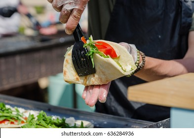 The chef prepares an Italian piad with vegetables, cheese and (if desired) with meat. This is a traditional meal at any fair in Europe.