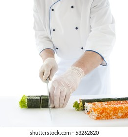 chef prepares Japanese food - sushi. On the table, the ingredients for sushi. Sushi-chef in white tunics slicks sushi rolls with a sharp knife