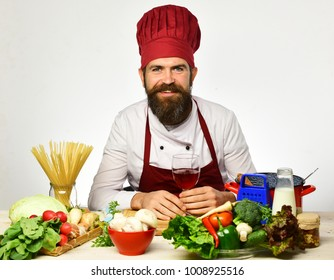 Chef prepares meal. Cook with happy face in burgundy uniform sits by kitchen table with vegetables, pasta and kitchenware. Man with beard holds wine glass on white background. Cooking process concept
