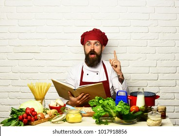 Chef prepares meal. Man with beard holds cook book on white brick wall background. Cook with shocked face in uniform sits by table with vegetables, pasta and kitchenware. Cooking process concept