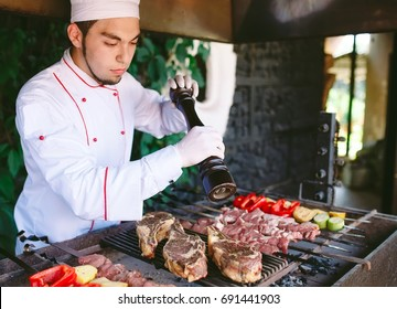 The Chef prepares meat on the barbecue.