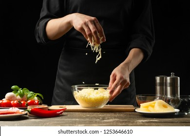 The chef prepares mozzarella cheese, cheddar for Italian pizza, pasta. On a black background, freezing in motion. A concept of tasty and healthy food. Design text, recipe book