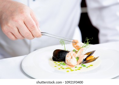 Chef prepares a seafood dish at a restaurant or hotel. Hand of a cook decorating a plate.