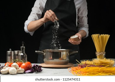 The chef prepares spaghetti and pasta, salt water, against a dark background, the concept of cooking