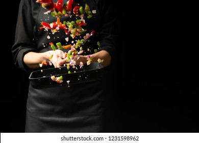 The chef prepares the vegetables on the pan. Black background for copying text. Restaurant business and advertising.